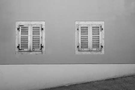 two old wooden windows on an old house shot from an uphill street in the city center Standard-Bild