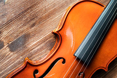 the detail of a violin on a wooden table