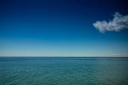 a cloud in the blue sky above the sea