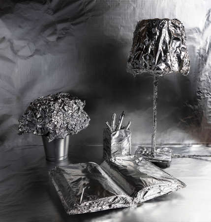 A lamp, a book and a plant pot wrapped in aluminum foil