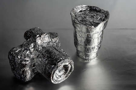 a camera and a lens wrapped in aluminum foil