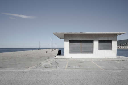 a closed building and the pier on the sea on a sunny day