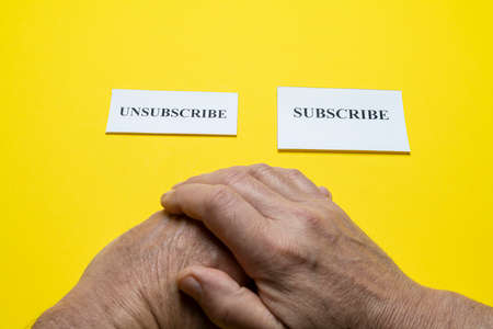 tickets with the word subscribe and unsubscribe in the hands of a man. The concept of choice.