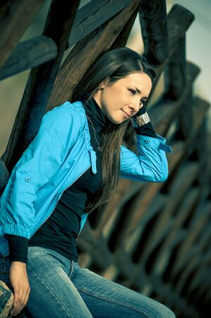 the beautiful girl is photographed on the street, sitting near a wooden protection Stock Photo - 17374500