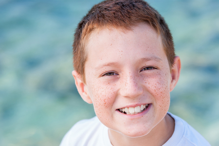 freckle: the beautiful cheerful red boy was photographed at the sea Stock Photo