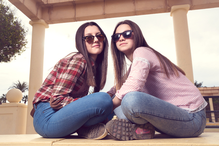 two girls: two girls were photografed in park on a bench