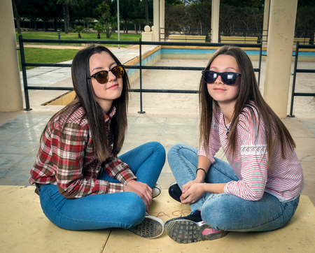 two girls: two girls were photographed in park on a bench