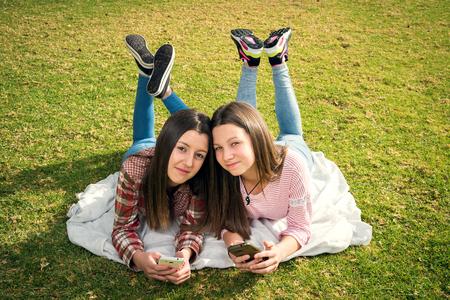 dos hermosas chicas jóvenes escriben en los teléfonos móviles situadas en el parque