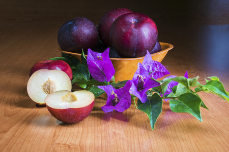 ripe juicy plums in a wooden plate were photographed in studio