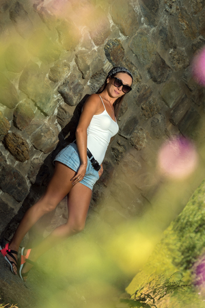 the stylish beautiful girl has been photographed on walk near a wall