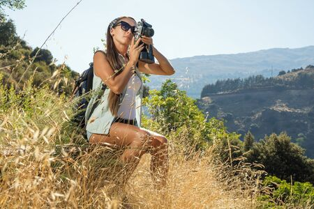 the beautiful girl the traveler with the camera has been photographed on walk in mountains