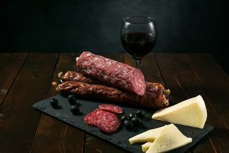 beautiful delicious dried sausage with a piece of cheese and olives, were photographed in the studio
