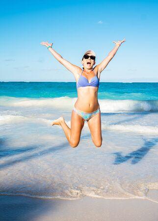 Beautiful girl in a high jump on the beach