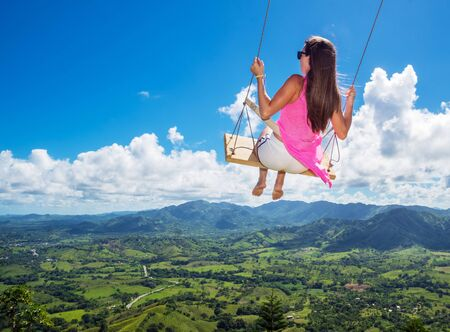 Beautiful girl steaming in the air on a large swing