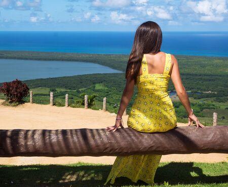 Beautiful girl in yellow dress looks at the ocean 免版税图像