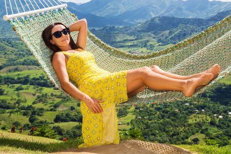 Cute beautiful girl in hammock in yellow dress amid nature 免版税图像