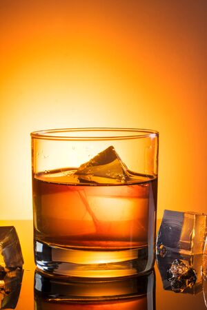 A simple glass of whiskey with ice was photographed on black glass Stock Photo