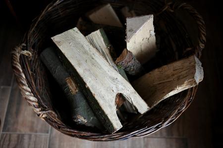 log basket: Old Basket of Cut Firewood on Rustic Wood Floor. Stock Photo