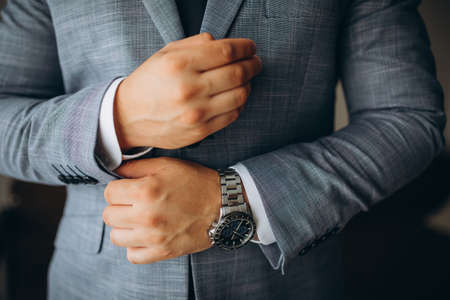 people, business, fashion and clothing concept - close up of man dressing up and fastening buttons on shirt at home. Imagens