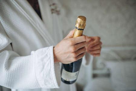 man open champagne bottle on white background