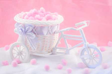 invents: Tricycle souvenir on a pink background with fluffy donuts.