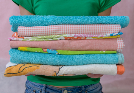 folded clothes: Woman holding folded clothes in hands. Closeup