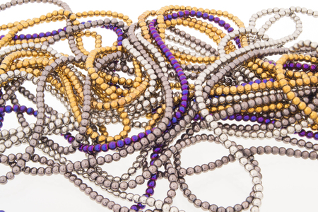 Line of golden beads garland thread isolated over the white background.