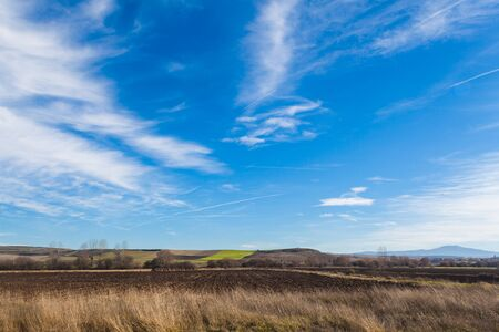 Landscape of brown farm fields with blue sky