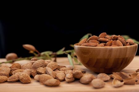 Shell and peeled almonds in wooden bowl on wooden table with a unfocussed almond tree branch with black background. Almonds concept with copyspace.