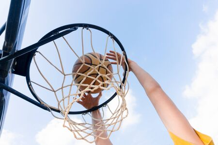 Young boy making a slam dunk in street basketball with blue sky and white clouds
