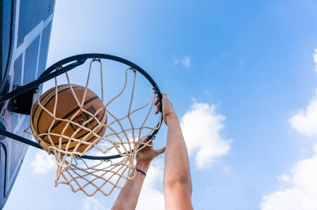 Young boy making a slam dunk in street basketball with blue sky and white clouds Stock Photo