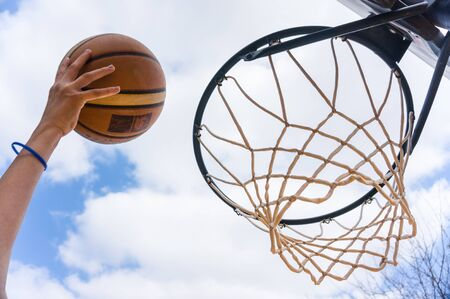 Lay up in street basketball with blue sky and white clouds