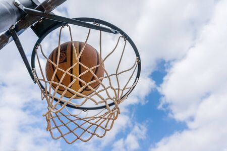 Basketball ball enter the basket in a swish shoot outdoors with blue sky Stock Photo
