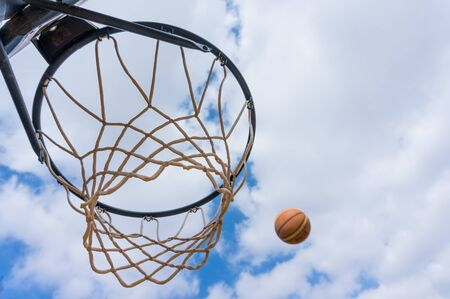 Basketball throw in street basketball with blue sky and white clouds