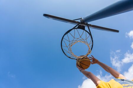 Slam dunk in basketball outdoors with blue sky