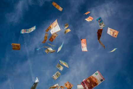Falling money from the blue sky with clouds