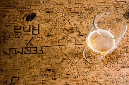 Empty glass of beer on an old table with graffiti