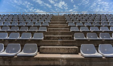 Empty grey stands at the stadium with blue sky