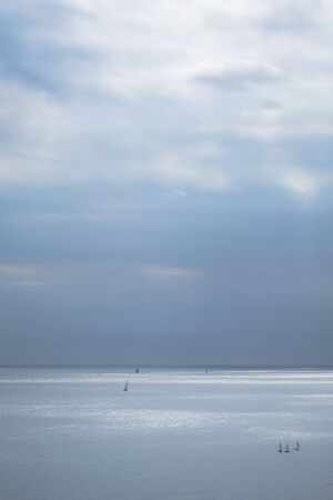 Calm blue sea with sailboats and cloudy sky