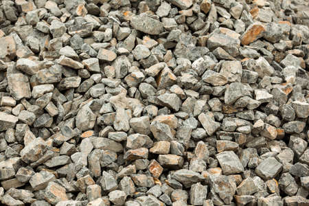 Background image of medium sized stones in gray. Building material, natural form boulders. The basis for the manufacture of concrete building structures.