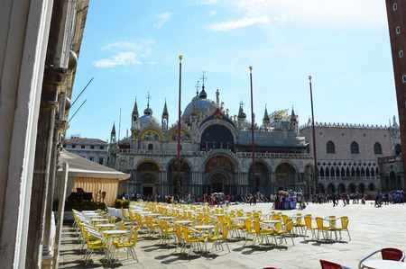 St Marks Square Venice with St Marks Basilica in sunny day, tables and chairs of a restaurant with tourists on the bottom, Venice, Italy summer 2016