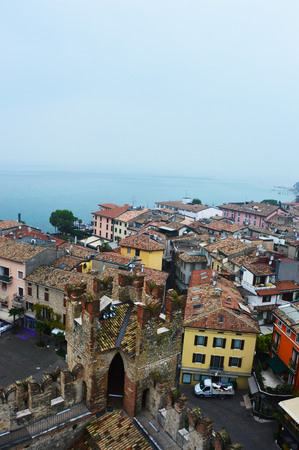 mistery: View of Sirmione town from the castle with fog Lake Garda in Italy