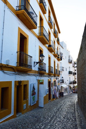 Typical alley of Dalt Vila, Eivissa, Ibiza island, with characteristic construction buildings white and yellow, stone road surface, on sunset, Ibiza, Spain, summer holidays 2016