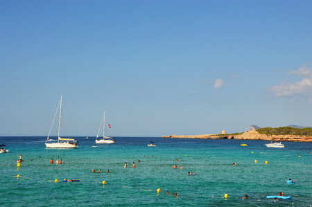 People enjoying life in Ibiza beach Cala Comte, amazing rocky beach with crystalline water and boats, natural paradisiac scenery, Ibiza island, Spain, holidays summer 2016 Stock Photo