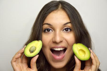 Portrait of attractive girl with avocado healthy fruit