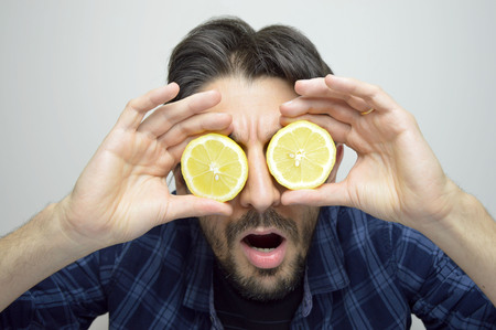 Young man covering his eyes with lemons and discovering surprised new thing / new product Imagens