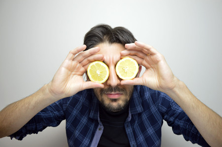 A curious young man covering his eyes with lemons discovering a new thing / new product