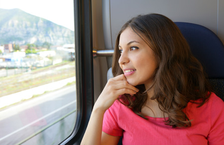 Young beautiful woman looking through the train window. Happy young woman sitting in the car. Modern people city lifestyle. Young urban woman.