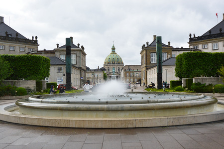 italian fountain: COPENHAGEN, DENMARK - MAY 31, 2017: fountain in Amalie Garden with two columns by Italian sculptor Arnaldo Pomodoro and on the background the dome of Frederiks Church and statue of King Frederick V