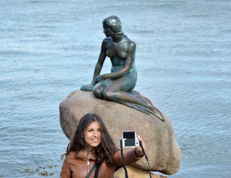 COPENHAGEN, DENMARK - MAY 31, 2017: tourist girl taking self photo with the bronze statue of the Little Mermaid, Den lille Havfrue, on the coastal rocks at the Langelinie promenade in Copenhagen